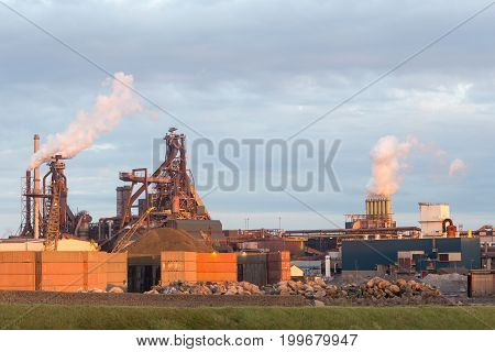 Old steel factory with smokestacks and chimney emissions