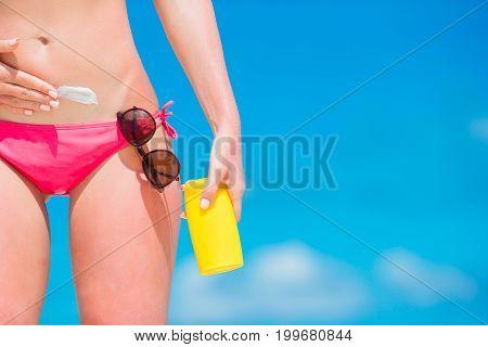 Closeup applying with sunscreen on white beach