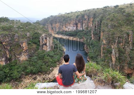 Couple On A Rock Overlooking A Canyon With A River On The Bottom And Rocky Walls Covered By Green Tr