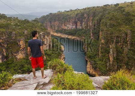 Man Standing On A Rock Overlooking A Canyon With A River On The Bottom And Rocky Walls Covered By Gr