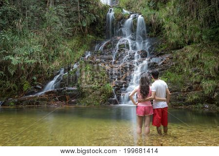 Couple At Waterfall. Beautiful Waterfall In The Forest. Natural Water Spring Waterfall.