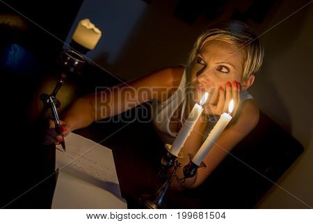 woman thinking and writing a letter under candles light