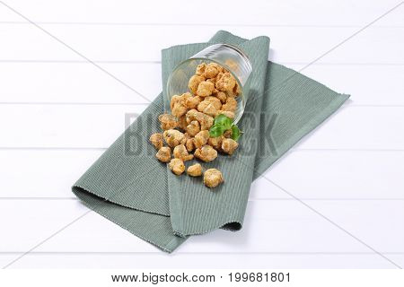 glass of soy meat cubes spilt out on grey place mat