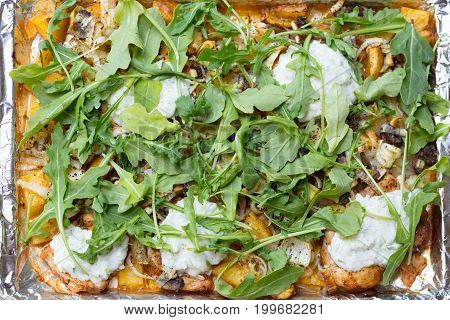 Oven roasted chicken and yukon gold potatoes leeks arugula and tzatziki sauce on a baking sheet lined with aluminum foil
