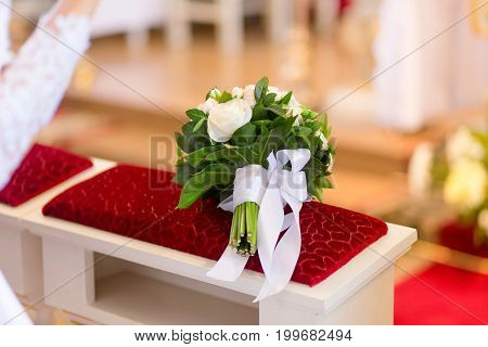Wedding Bouquet Laying On Bench In Church
