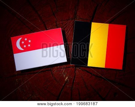 Singaporean Flag With Belgian Flag On A Tree Stump Isolated