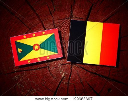 Grenada Flag With Belgian Flag On A Tree Stump Isolated