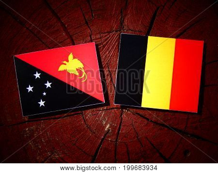 Papua New Guinea Flag With Belgian Flag On A Tree Stump Isolated