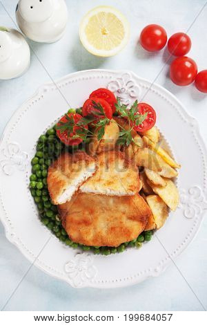 Breaded chicken steak with green peas and roasted potato
