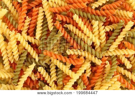 Food background - uncooked three-colored Fusilli durum wheat pasta with spinach and tomato