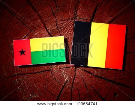 Guinea Bissau Flag With Belgian Flag On A Tree Stump Isolated