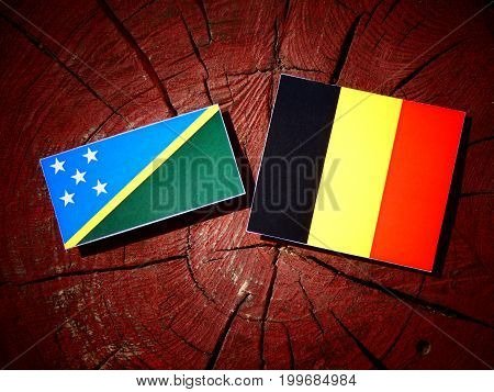 Solomon Islands Flag With Belgian Flag On A Tree Stump Isolated