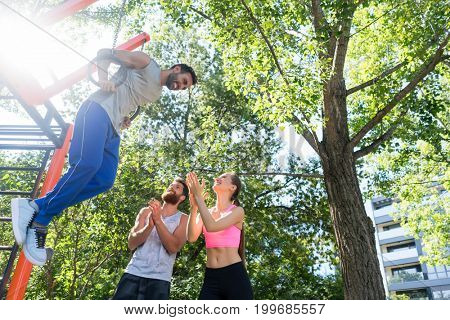 Low-angle view of a strong young man doing difficult dip exercise for triceps on gymnastic rings during street workout routine motivated by his friends
