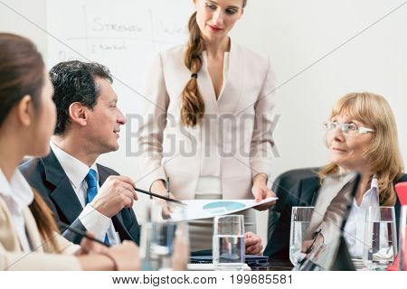Dedicated manager sharing his opinion while interpreting a pie chart during board of directors meeting in the conference room of a prosperous company