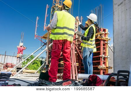 Low-angle view of an experienced female architect or manager guiding the workers while supervising their work on the construction site