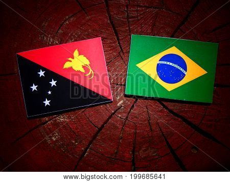 Papua New Guinea Flag With Brazilian Flag On A Tree Stump Isolated