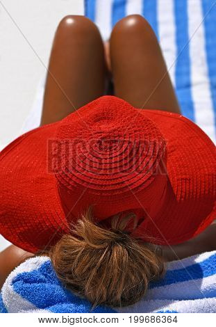 Attractive Woman Wearing A Red Summer Hat sunbathing on the Beach