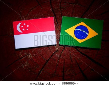 Singaporean Flag With Brazilian Flag On A Tree Stump Isolated