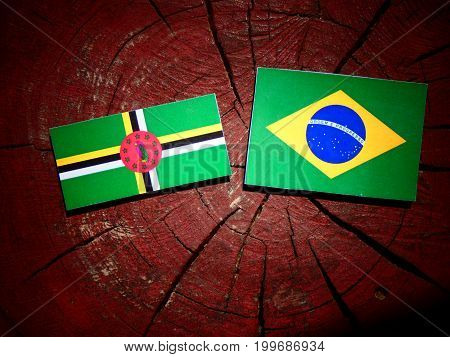 Dominica Flag With Brazilian Flag On A Tree Stump Isolated