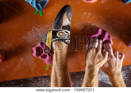 Cropped view of rock climber's hands and foot on holds in indoor climbing gym