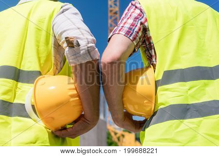 Close-up rear view of the hands of two workers wearing reflective safety vests while holding yellow hard hats outdoors on the construction site