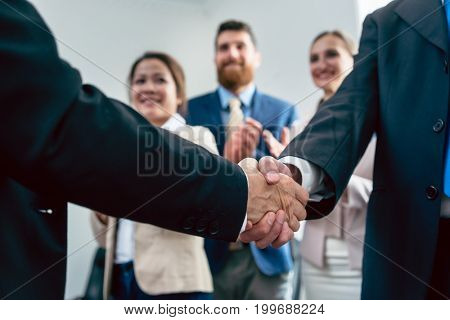 Close-up on handshake of two business men in applauses of three employees, after an important agreement for the success of the company