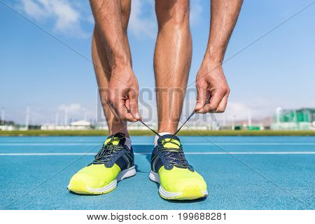 Runner tying running shoes laces on run tracks lanes in stadium getting ready for race competition outdoor on track and field. Sport athlete man jogging motivation.