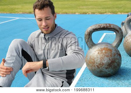 Fitness man checking smartwatch during workout strength training at weightlifting kettlebells outdoor gym. Healthy active lifestyle.