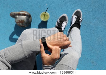Gym man touching smartwatch screen during workout strength training. Top view from above: kettlebell weights, green smoothie, body and legs. POV of athlete sitting resting. Healthy fitness lifestyle.