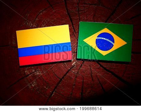 Colombian Flag With Brazilian Flag On A Tree Stump Isolated
