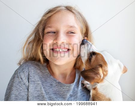 Happy child with dog. Portrait girl with pet. Jack Russell whispers a secret to teen