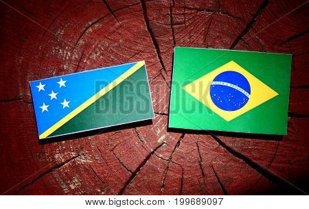 Solomon Islands Flag With Brazilian Flag On A Tree Stump Isolated