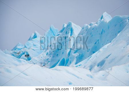 Slopes of the blue glacier against the sky. Beautiful blue glacier against the sky. Uneven surface of the glacier in the sun. The rays of the sun fall on the snow cover of the glaciers.