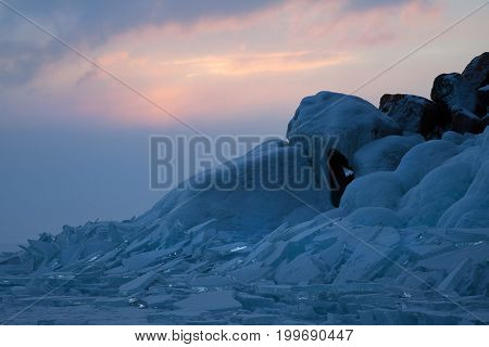 Glowing blue ice blocks on sunset background, fairytale winter landscape in soft colors