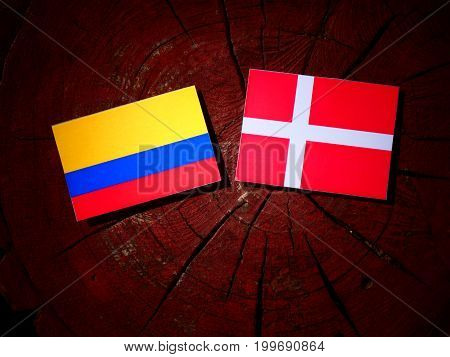 Colombian Flag With Danish Flag On A Tree Stump Isolated