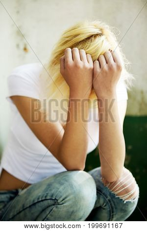 Sad young teenage girl is sitting and covering her face with hands.