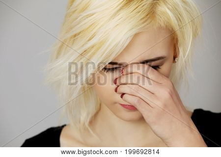 Young woman with sinus pain , isolated on white.