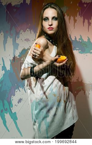 Young woman with dark makeup squeezing a orange