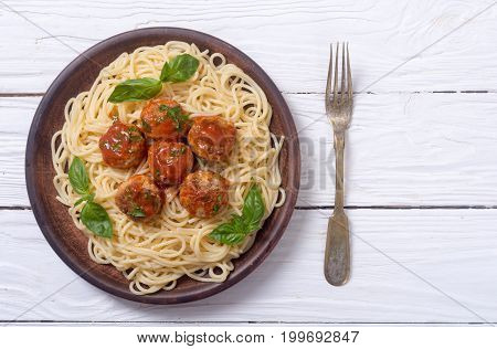 Spaghetti in plate with meatballs and basil . Top view space for text