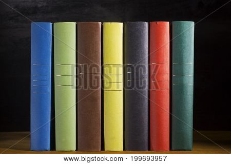 Books in multicolored covers on the wooden table