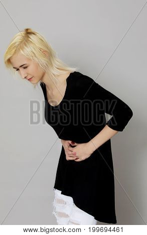 Young woman is suffering of stomachache. Medical problem.
