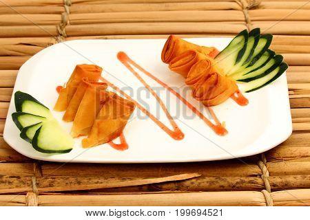 Comida Japonesa -  Harumaki de camarão com decoração em pepinos e molho agridoce