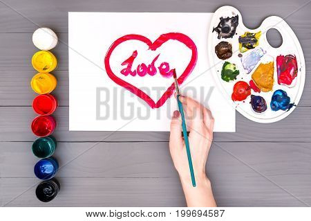 Artist's hand draws heart with the inscription love on sheet of white paper near open cans of colored paints and palette on grey wooden board.