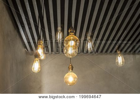 Hanging light bulbs over grey dark strip ceiling. Closeup