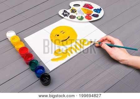 Artist's hand draws smile with the inscription smile on sheet of white paper near open cans of colored paints and palette on grey wooden board.
