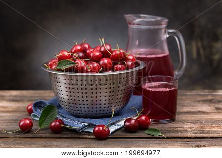Ripe sweet cherry in a colander on a wooden board and jug with juice on a dark background