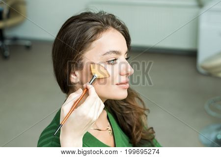 Closeup portrait of a woman applying dry cosmetic tonal foundation on the face using makeup brush. Makeup detail.