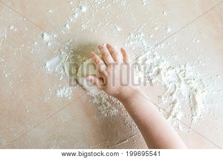 Top view shoot of children's hands make dough on the table
