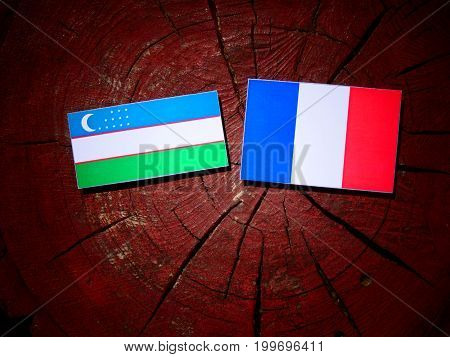 Uzbekistan Flag With French Flag On A Tree Stump Isolated
