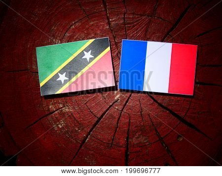Saint Kitts And Nevis Flag With French Flag On A Tree Stump Isolated